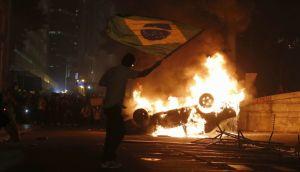 A demonstrator waves a Brazilian flag by a burning a car in downtown Rio de Janeiro